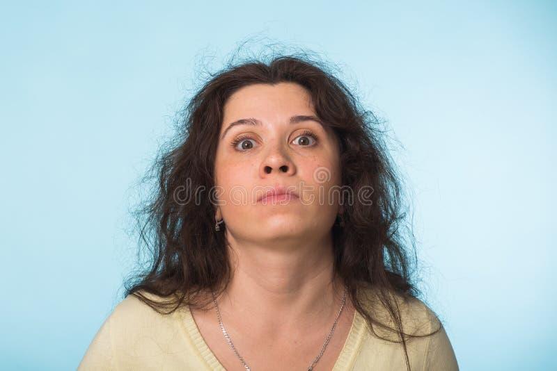 Chiuda sul ritratto di bella giovane donna con capelli ricci su fondo blu fotografia stock