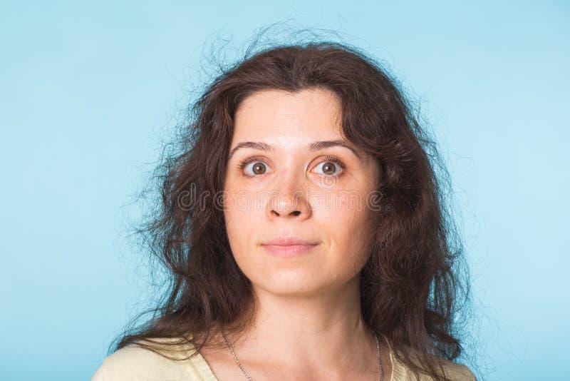 Chiuda sul ritratto di bella giovane donna con capelli ricci su fondo blu immagine stock