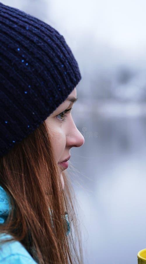 Chiuda sul ritratto di bella ragazza che sogna esaminando la distanza che sta all'aperto con la tazza di tè fotografia stock libera da diritti
