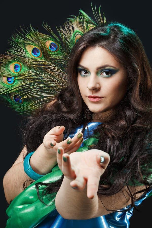 Chiuda sul ritratto di bella ragazza con la piuma del pavone, richiami di bellezza, chiamanti le mani Pavone creativo di trucco immagine stock libera da diritti