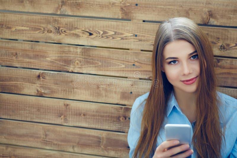 Chiuda sul ritratto di bella ragazza con lo Smart Phone in mani che si siedono sui precedenti della parete dei bordi di legno fotografia stock libera da diritti