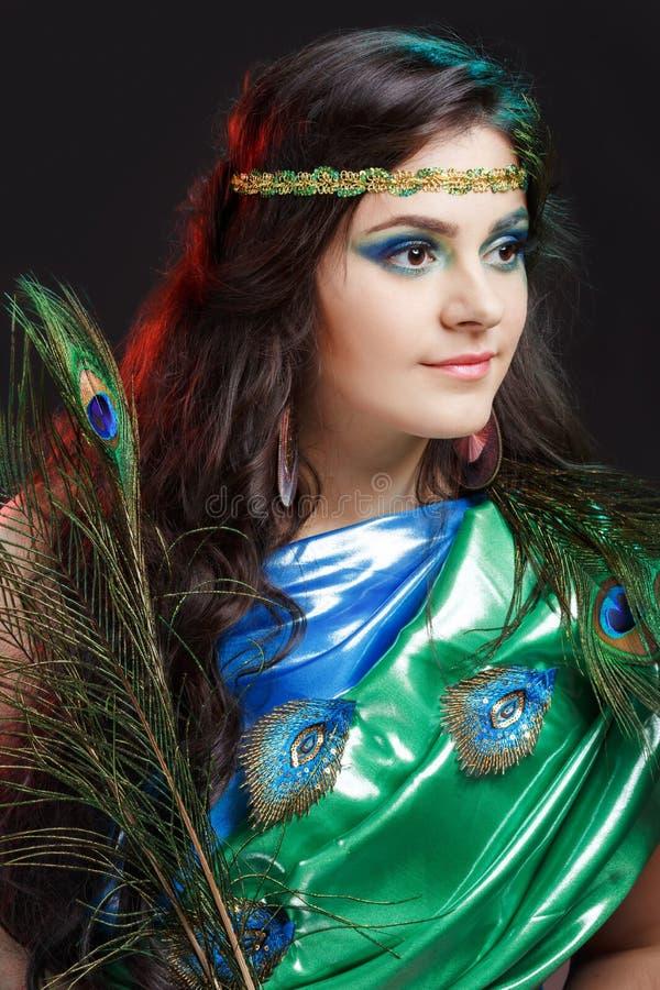 Chiuda sul ritratto di bellezza di bella ragazza con la piuma del pavone, fascia Piume creative del pavone di trucco attraente fotografia stock