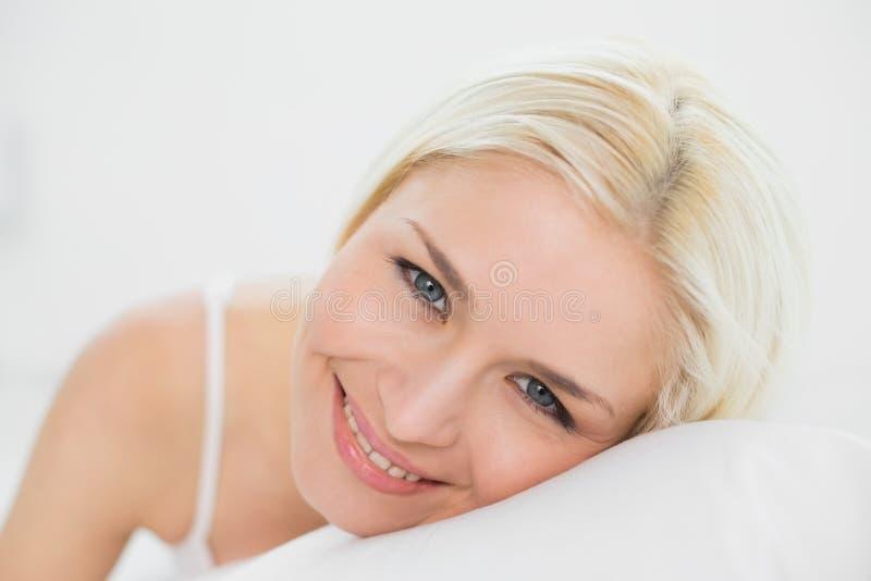 Chiuda sul ritratto di bello biondo a letto immagine stock