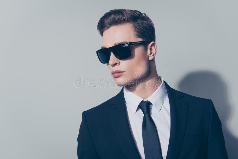 Chiuda sul ritratto di bello uomo alla moda in vestito nero e fotografia stock