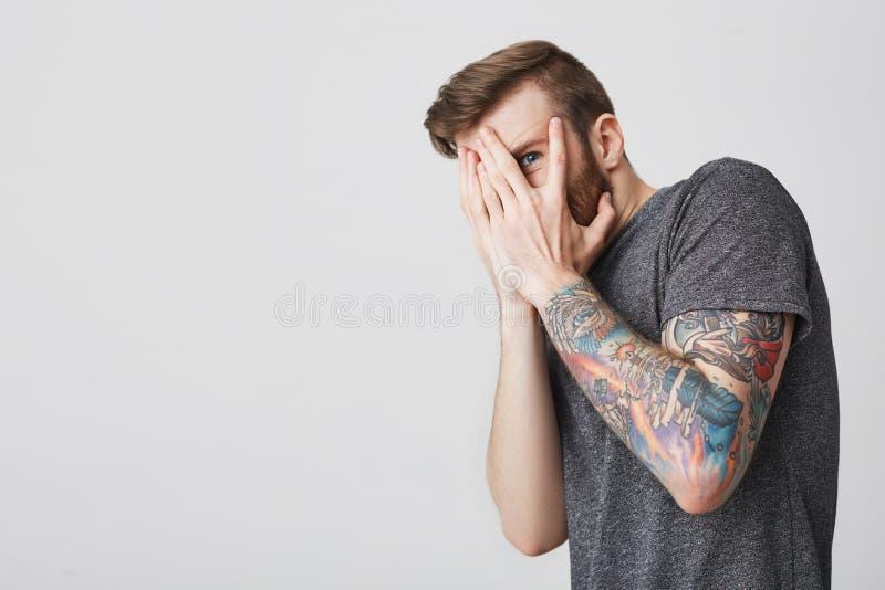 Chiuda sul ritratto di giovane bello tipo tattoed barbuto con breve taglio di capelli alla moda in maglietta grigia casuale fotografia stock libera da diritti