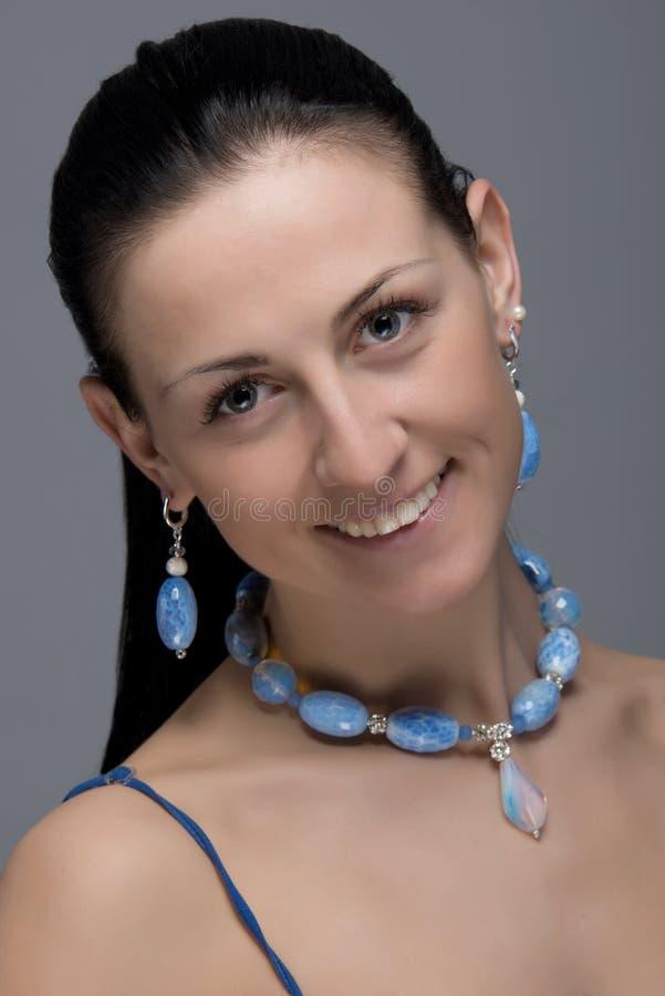 Ritratto della ragazza allegra con gli orecchini e la collana fotografia stock libera da diritti