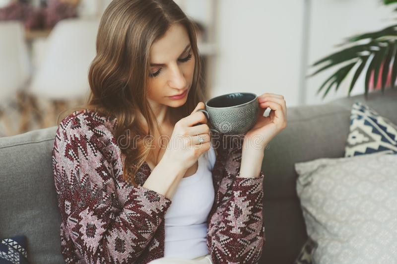 Chiuda sul ritratto di giovane donna premurosa con la tazza di tè o di caffè che si siede da solo a casa fotografia stock