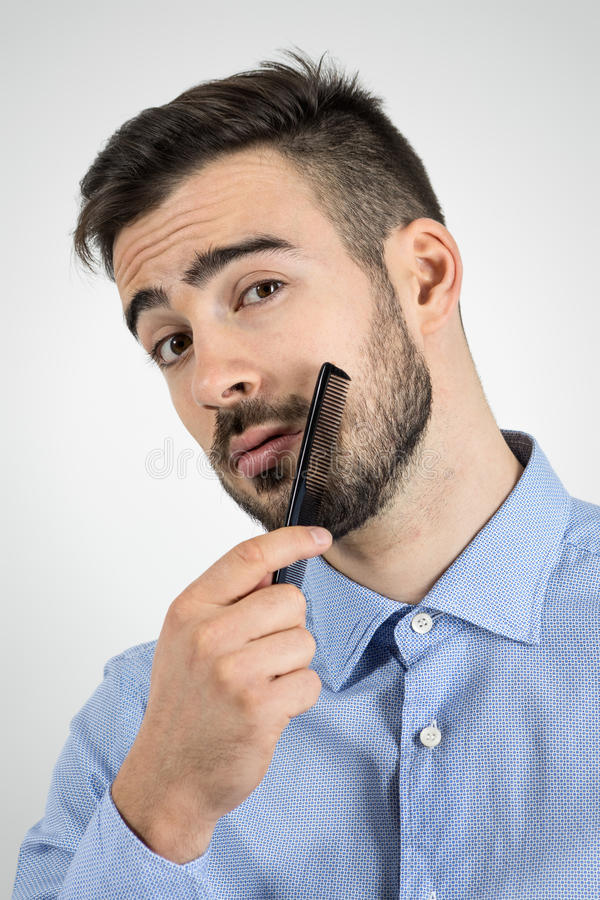 Chiuda sul ritratto di giovane uomo barbuto che pettina la sua barba che esamina la macchina fotografica fotografia stock