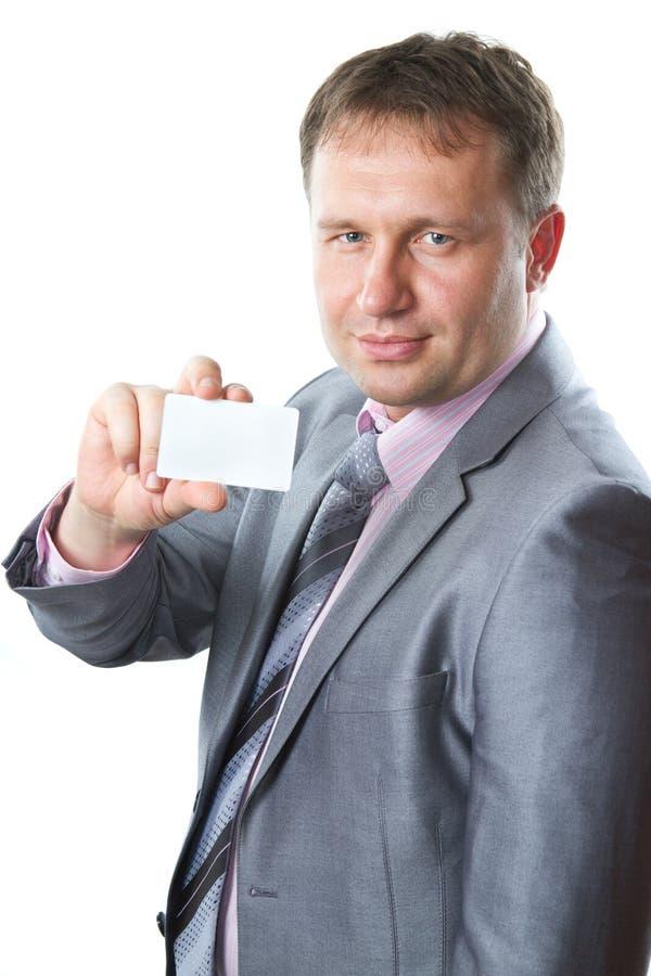 Chiuda sul ritratto di giovane uomo bello di affari in un vestito alla moda che tiene il biglietto da visita in bianco, spazio del fotografie stock libere da diritti