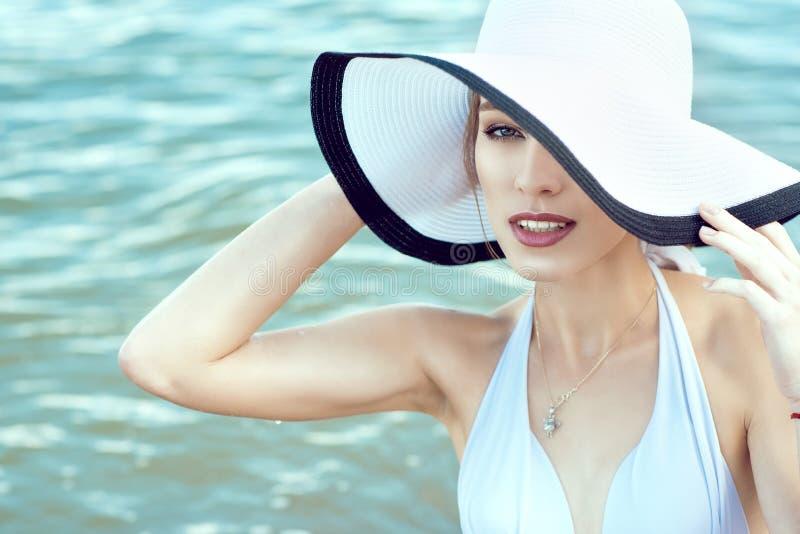 Chiuda sul ritratto di signora affascinante elegante splendida che nasconde la metà del suo fronte dietro l'ampio cappello del bo immagini stock