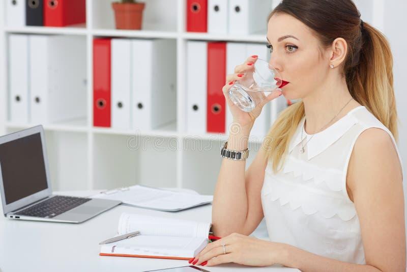 Chiuda sul ritratto di un'acqua potabile della bella giovane donna al posto di lavoro immagini stock