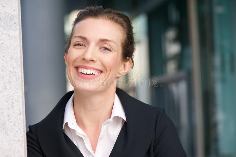 Chiuda sul ritratto di un sorridere amichevole della donna di affari immagini stock
