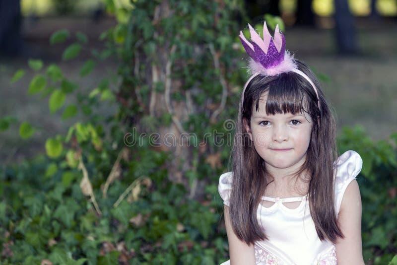 Chiuda sul ritratto di una bambina dolce con una corona sul suo hea immagine stock libera da diritti