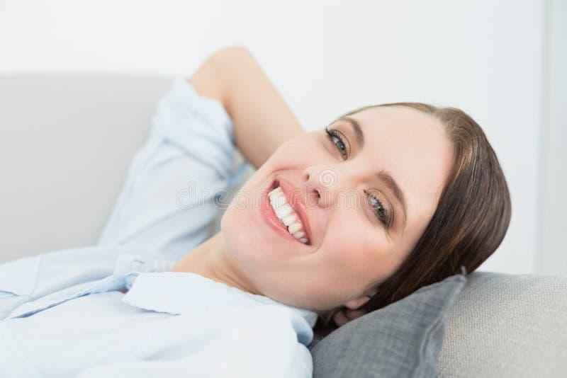 Chiuda sul ritratto di una donna ben vestito sorridente che si rilassa sul sofà fotografie stock libere da diritti