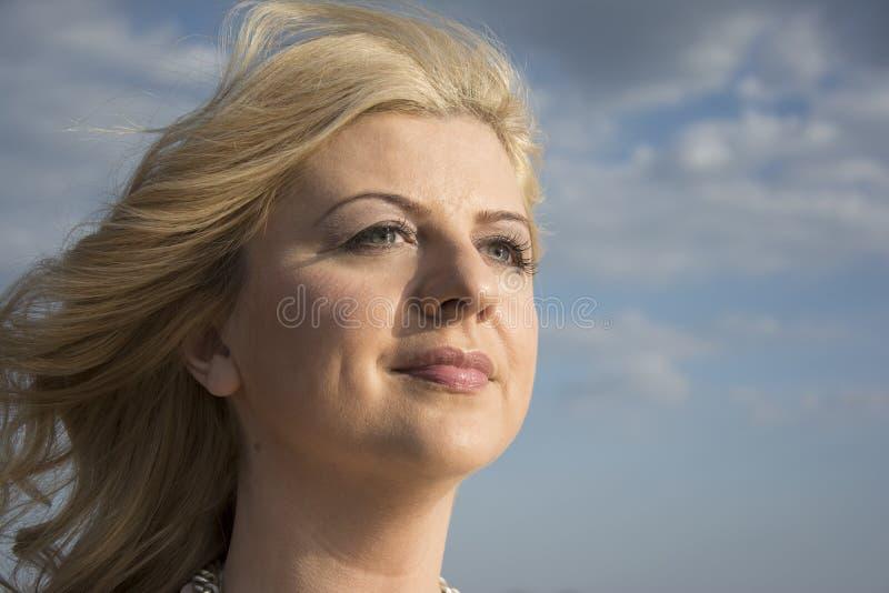 Chiuda sul ritratto di una donna mentre salto del vento fotografia stock libera da diritti