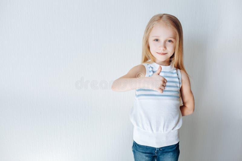 Chiuda sul ritratto di una ragazza sveglia che ride con i pollici su su fondo bianco Copi lo spazio immagine stock libera da diritti