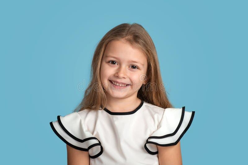Chiuda sul ritratto emozionale di giovane ragazza sorridente bionda che indossa blous bianco con le strisce nere su fondo blu in  fotografie stock
