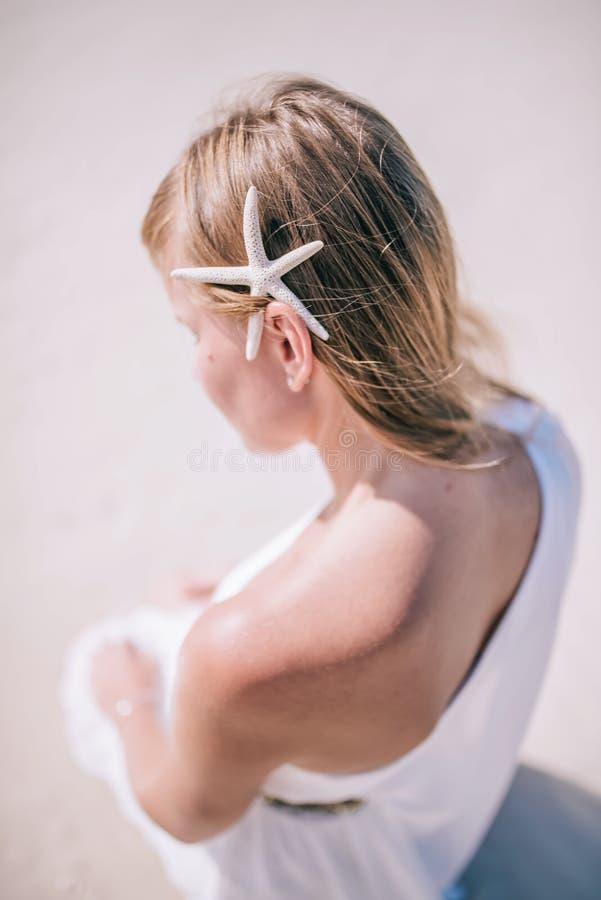 Chiuda sul ritratto facciale all'aperto di giovane modello biondo che si siede sulla spiaggia di sabbia bianca con una stella mar fotografie stock