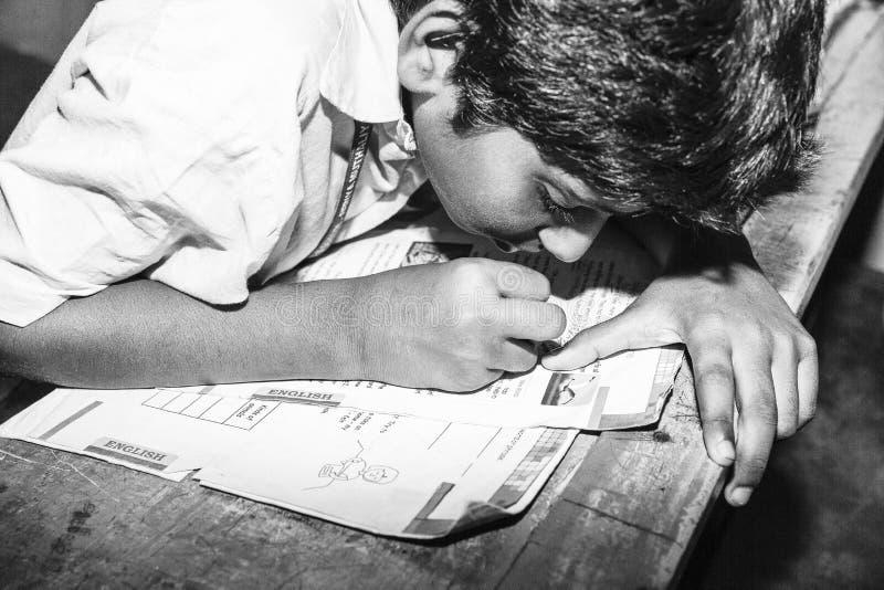 Chiuda sul ritratto giovane, il piccolo uomo senza vetri, libro di lettura, incontrando difficoltà per vedere il testo al chool C fotografia stock libera da diritti