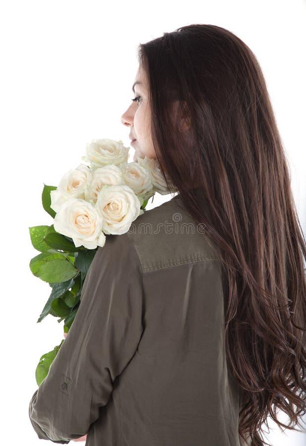 Chiuda sul ritratto potato della donna ispanica allegra affascinante con trucco naturale che ha mazzo delle rose bianche in mani  fotografia stock