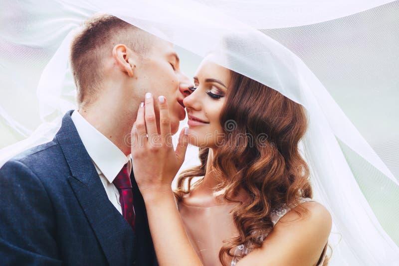 Chiuda sul ritratto romantico di belle coppie di nozze sotto il velo immagini stock