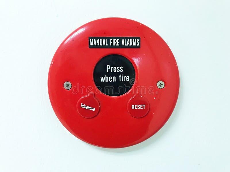 chiuda sul segno rosso dell'allarme antincendio con il manuale fotografia stock
