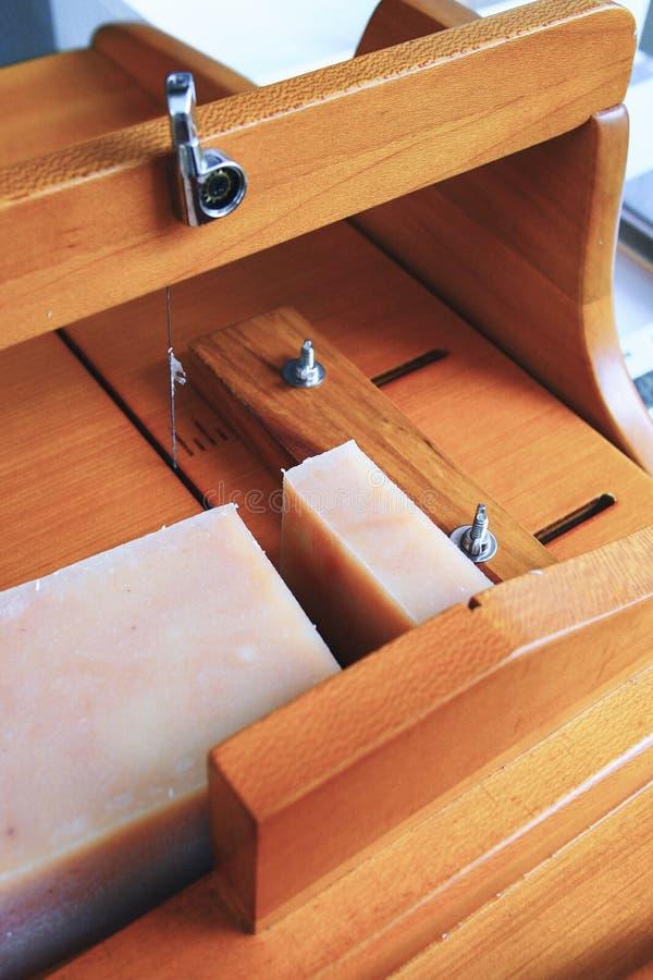 Chiuda sul taglio del sapone casalingo con una taglierina di legno fotografia stock