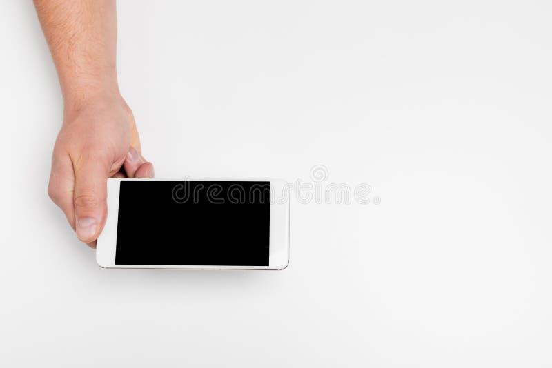 Chiuda sul telefono isolato su bianco, schermo in bianco della tenuta della mano di colore bianco dello smartphone del modello immagine stock libera da diritti