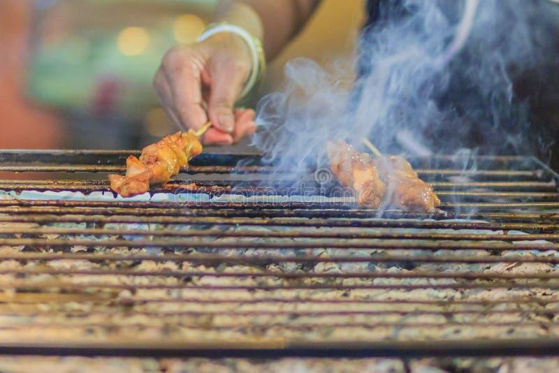 Chiuda sul venditore che griglia la carne di maiale satay nel fumo, bistecca tailandese fotografie stock libere da diritti