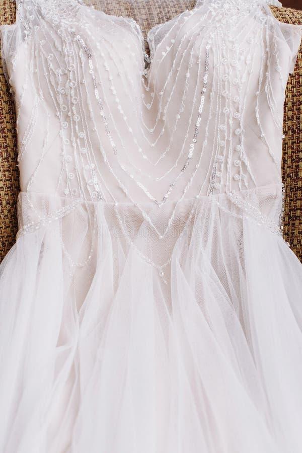 Chiuda sul vestito da sposa bianco con bello pizzo e sulle perle che si trovano sulla poltrona Mattina del ` s della sposa fotografia stock libera da diritti