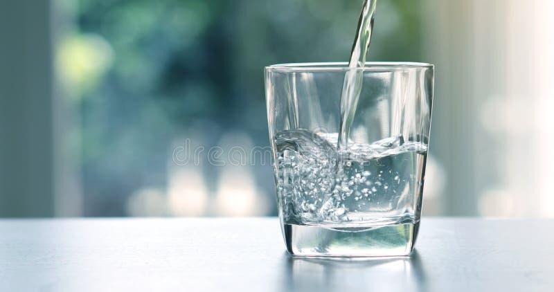 Chiuda sull'acqua fresca purificata di versamento della bevanda dalla bottiglia fotografia stock