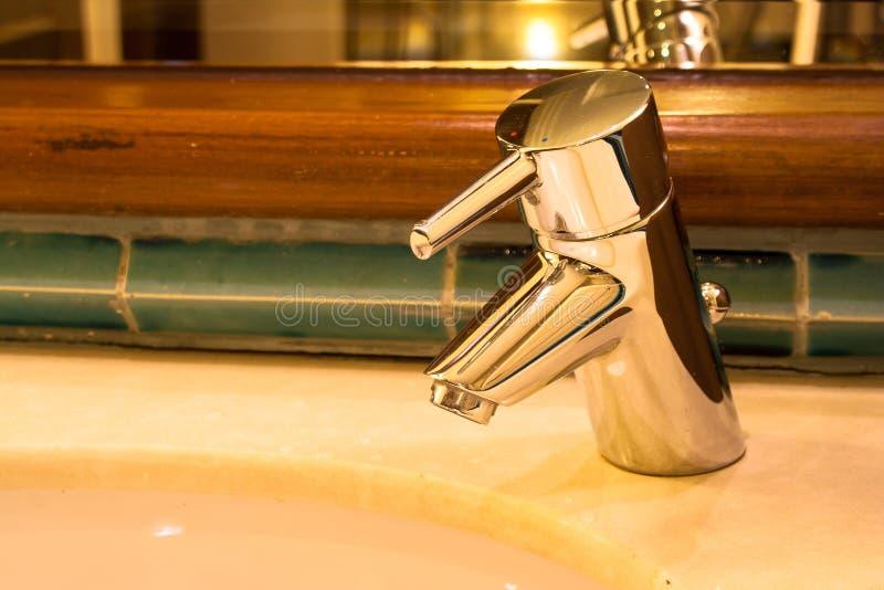 Chiuda sull'acqua inossidabile del rubinetto sopra il lavabo in bagno fotografia stock