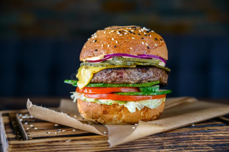 Chiuda sull'hamburger fresco delizioso sul bordo di legno fotografia stock libera da diritti