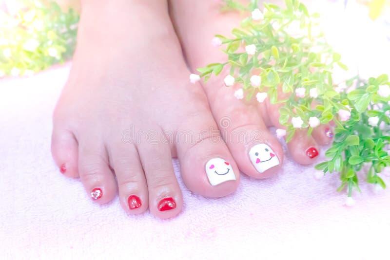Chiuda sull'immagine dell'unghia del piede della pittura nel cuore differente de degli zecchini immagine stock