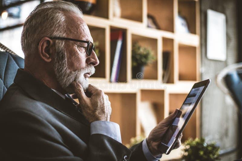 Chiuda sull'immagine dell'uomo senior che lavora alla linguetta digitale immagine stock
