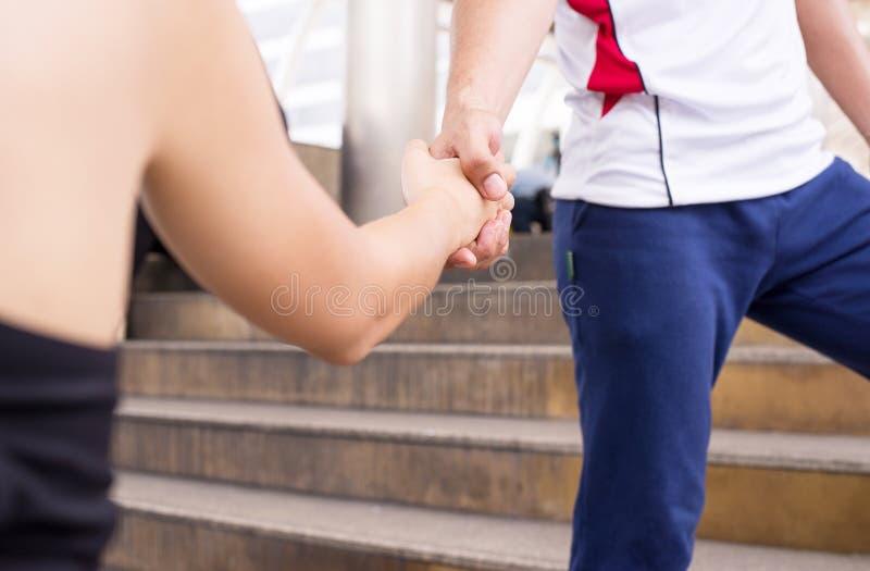 Chiuda sull'immagine delle coppie attraenti di sport che stringono la mano, stretta di mano della gente che sta all'aperto fotografia stock libera da diritti