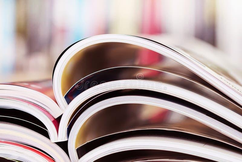 chiuda sull'impilamento della rivista aperta con il backg confuso dello scaffale per libri fotografia stock libera da diritti