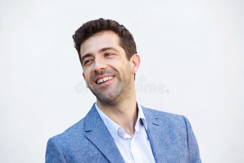 Chiuda sull'uomo bello che sorride contro il fondo bianco immagini stock libere da diritti