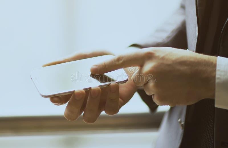Chiuda sull'uomo che per mezzo dello Smart Phone mobile all'aperto fotografia stock libera da diritti