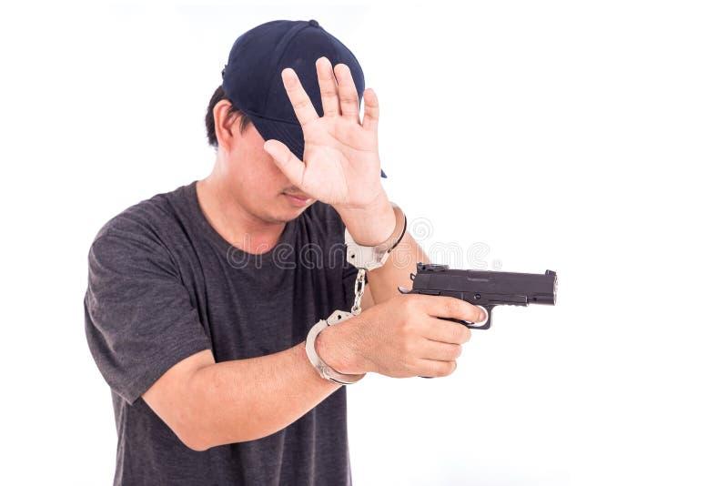 Chiuda sull'uomo con le manette e la pistola sulle mani isolate su bianco fotografia stock