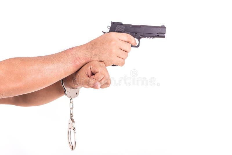 Chiuda sull'uomo con le manette e la pistola sulle mani isolate su bianco immagini stock libere da diritti