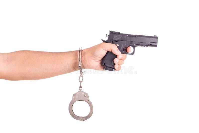 Chiuda sull'uomo con le manette e la pistola sulle mani isolate su bianco fotografie stock
