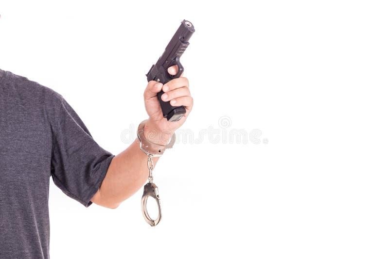 Chiuda sull'uomo con le manette e la pistola sulle mani isolate su bianco fotografia stock libera da diritti