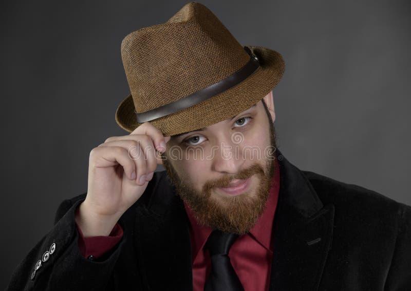 Chiuda sull'uomo del pizzo che tiene il suo cappello di Brown fotografia stock