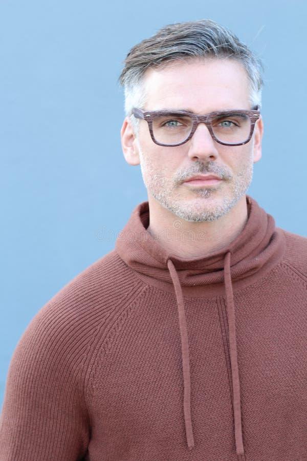 Chiuda sull'uomo di medio evo che indossa il maglione e gli occhiali di Brown che sorridono alla macchina fotografica, su fondo b immagine stock libera da diritti