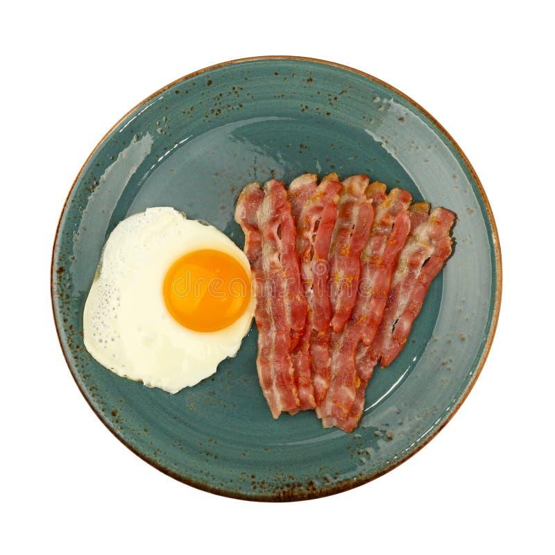 Chiuda sull'uovo e sul bacon laterali soleggiati sul piatto blu fotografie stock
