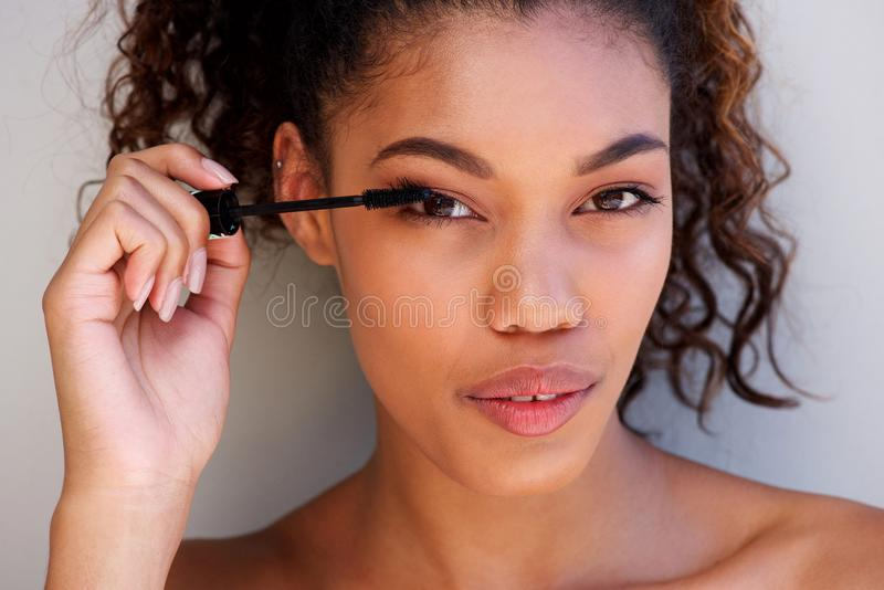 Chiuda sulla bella donna afroamericana che mette sopra compongono immagini stock