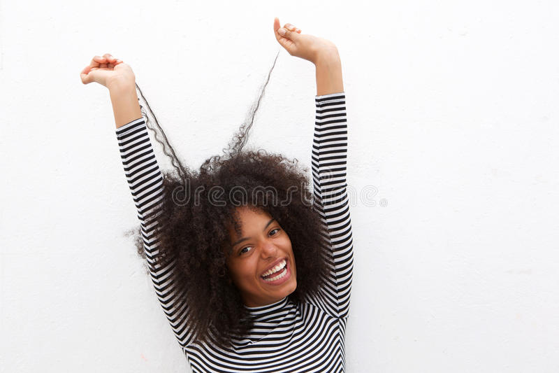 Chiuda sulla bella donna di colore felice che tira i capelli ricci fotografia stock