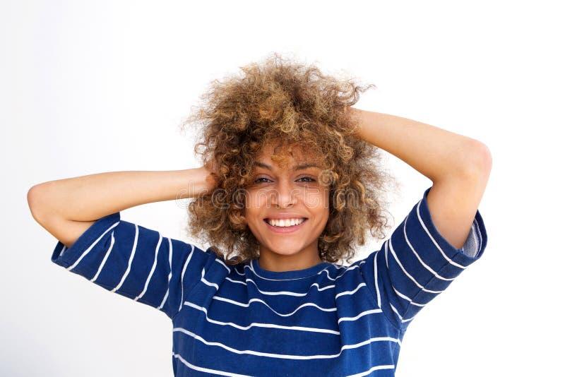 Chiuda sulla bella giovane donna afroamericana che sorride con le mani in capelli contro la parete bianca fotografia stock