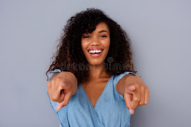 Chiuda sulla bella giovane donna di colore che sorride e che indica le dita immagine stock libera da diritti